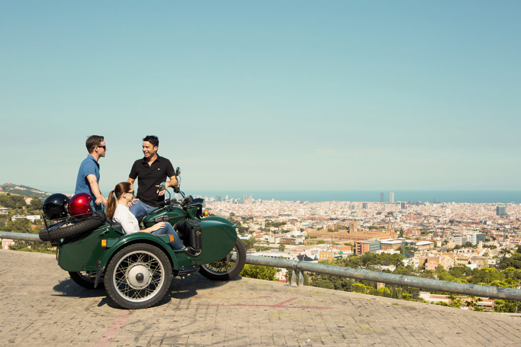 Private guide chats with travellers sitting on motorcycle and sidecar overlooking Barcelona.
