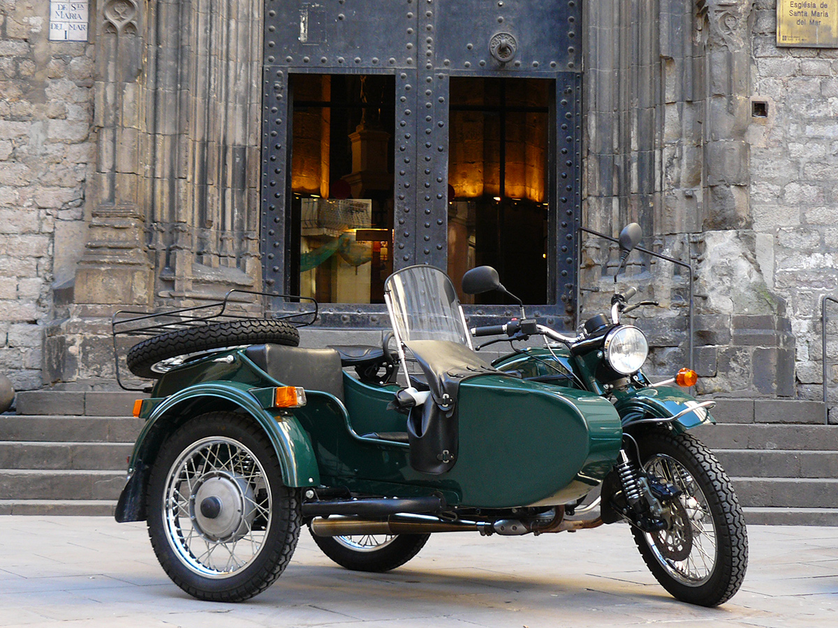 A green sidecar motorcycle in front of medieval church doors.