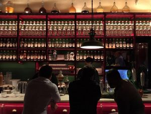 people having a coktail inside bar with bottles on the background.