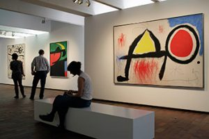 Girl sitting on a bech inside the miro museum with paintings on the background.