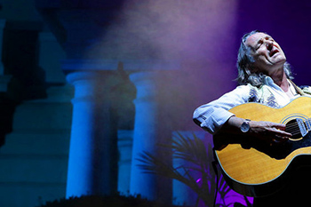 singer on a stage playing passionally his guitar