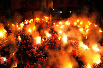 crowd holding torches in a spanish square