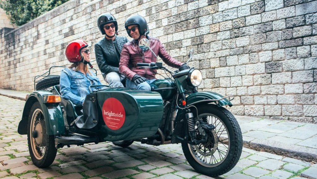 brightside tours sidecar motorcycle with passengers chatting in barcelona