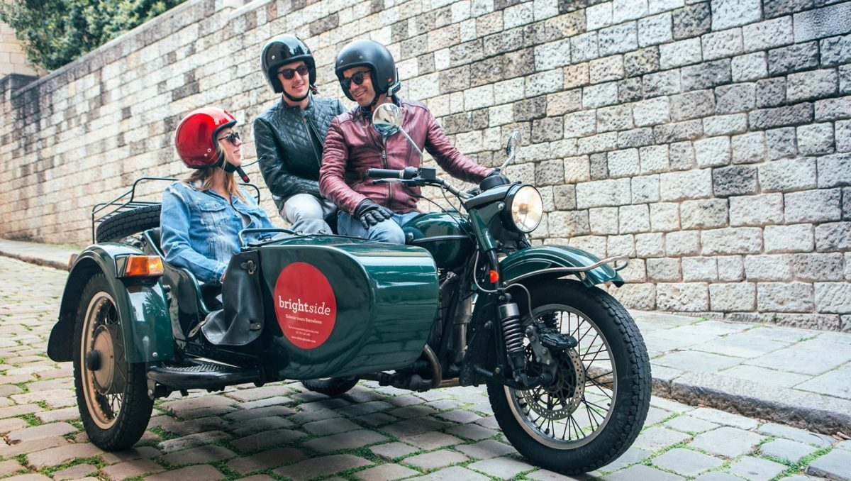 Sidecar motorcycle with passengers touring Barcelona.