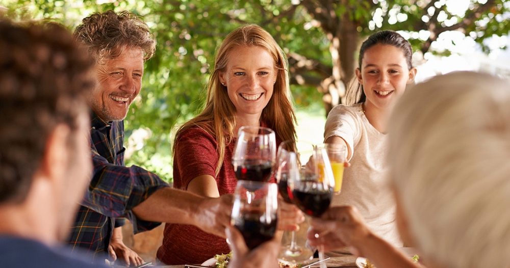 Family smiling and toasting with glasses of wine during a tour in Penedes