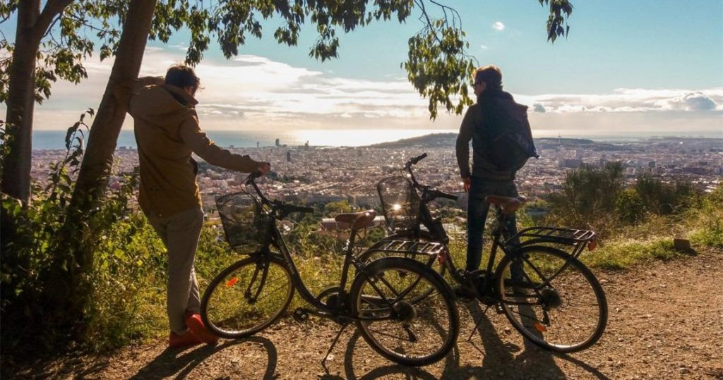 Two men standing next to bicycles watching the view of barcelona.