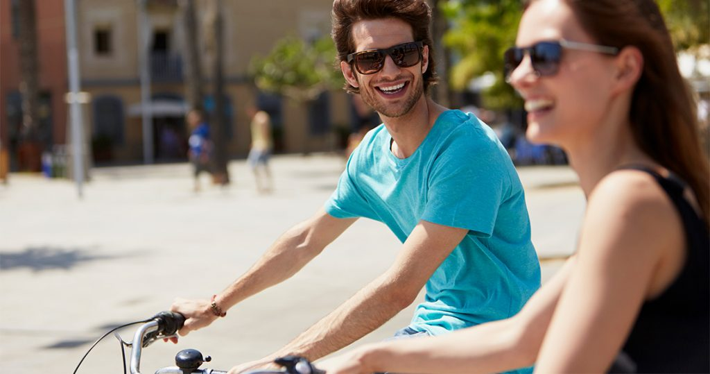 Young couple riding two bicycles in barcelona
