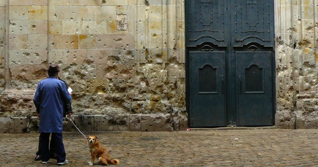 man with dog standing next to wall in barcelona plaza sant felip neri plaza
