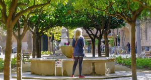 woman standing next by trees in a garden with fountain in barcelona old city