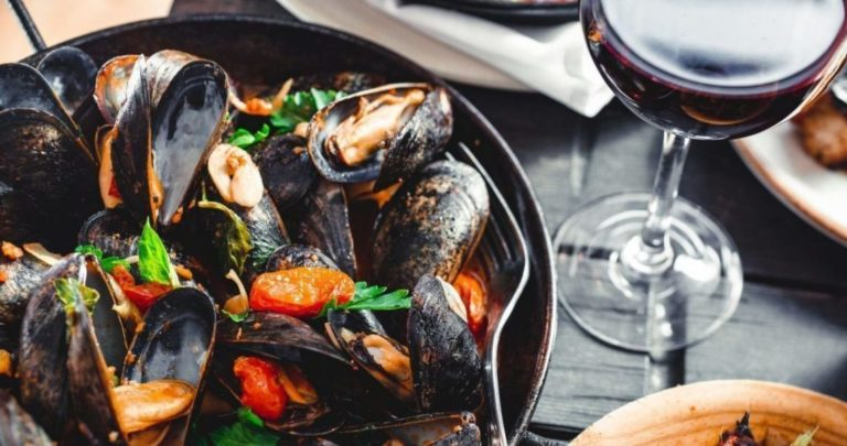 steamed mussels with wine glass on private ta