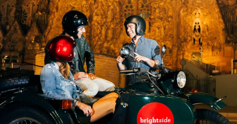 Brightside tours guide talks to passengers sitting on the sidecar motorcycle with sagrada familia church on the backgroud during a barcelona night tour